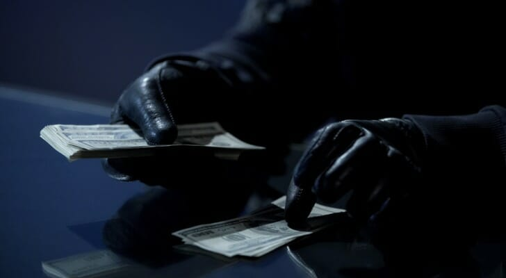 Criminal with gloves stealing money