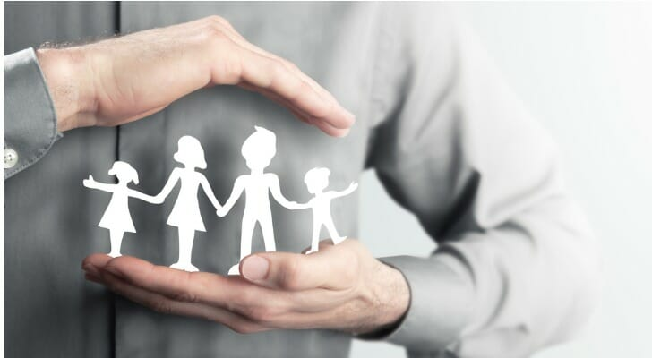 Man holding paper cutout of family members