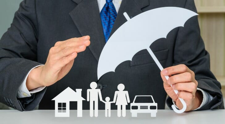Insurance broker holding a picture of an umbrella over a picture of a family.