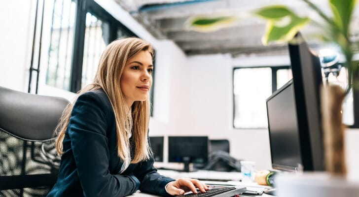 Image shows a young woman financial advisor wearing a black suit sitting at a desk and working at a computer station. In this study, SmartAsset identified the best cities for young financial advisors to start their careers.
