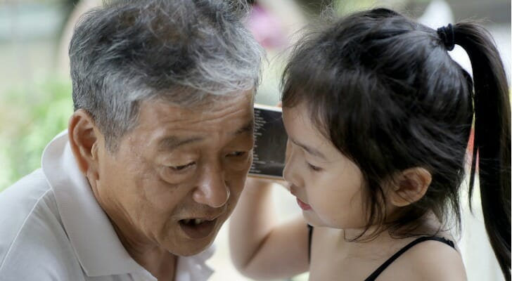 Grandfather and granddaughter listening to the same smartphone