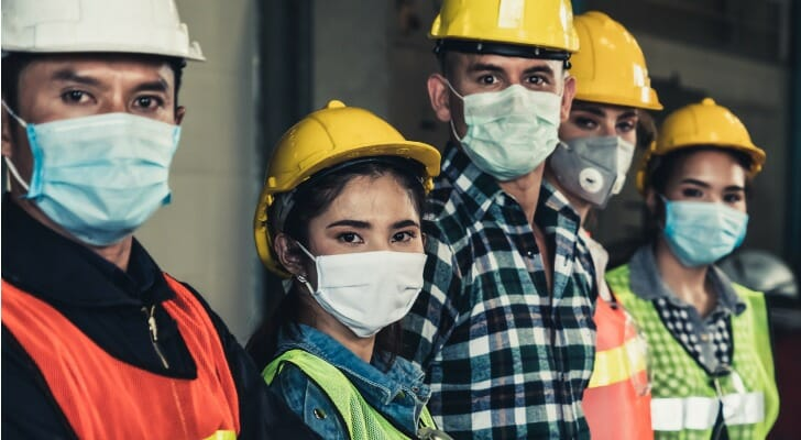 Image shows five construction workers wearing hard hats, work uniforms and masks to protect against COVID-19. In this study, SmartAsset analyzes BLS data to identify COVID-19's long-term impact on jobs.