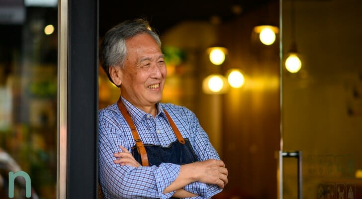 Image shows a senior employee standing in the doorway of his workplace. SmartAsset analyzed BLS data to find recent employment trends among seniors.