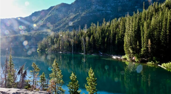 Image shows the sun shining brightly over a clear lake surrounded by evergreen trees at the foot of a mountain in the Pacific Northwest. In this study, SmartAsset analyzed various data sources to find the best places for outdoor enthusiasts to live and work.