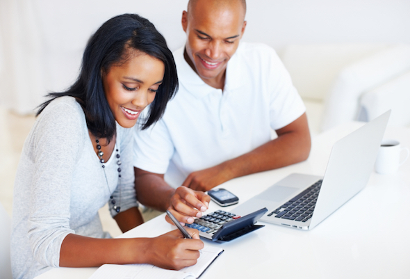 Couple working on budget with calculator, computer and notebook - Budgeting Tips