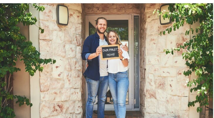 A young couple standing in front of their first house
