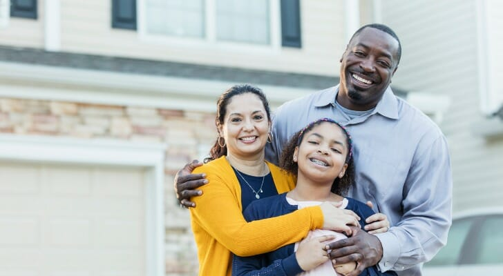 Image shows a mixed-race family of three standing and smiling in front of their new home. In this study, SmartAsset analyzed data across four categories - market favorability, affordability, livability and employment - to find the best cities for first-time homebuyers.