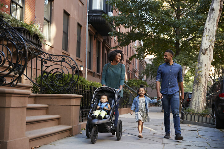 Image shows a Black American family walking down a tree-lined street. SmartAsset used data related to income, homeownership and more to determine the cities where Black Americans fared best economically leading up to 2020.