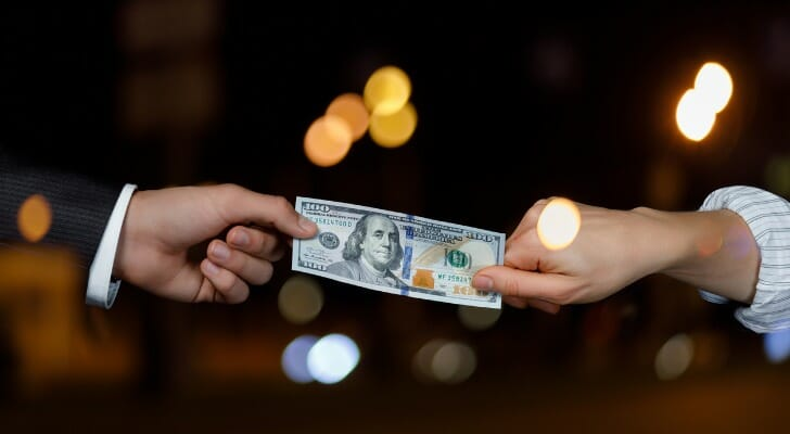 Two people tugging on a $100 bill