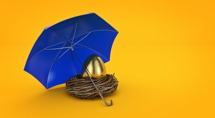 A golden egg, resting in a nest with an umbrella over it