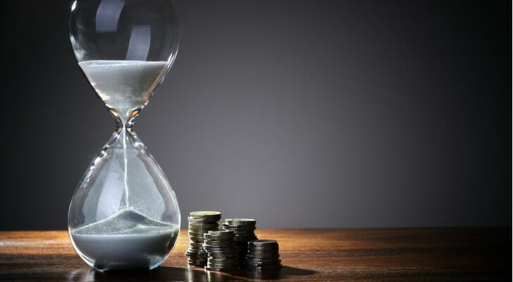 Hour glass next to cash