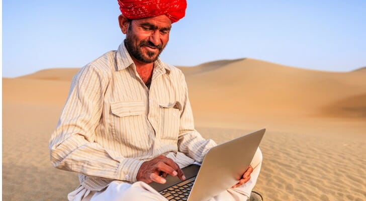 Indian man using a digital device as he sits on a sand dune