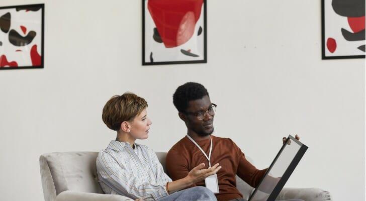 Art investors examine a painting