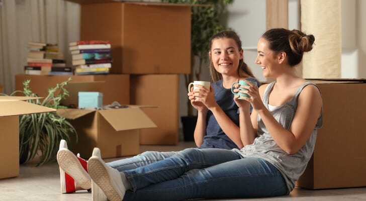 Two roommates sit in their new apartment and enjoy a cup of coffee on moving day. SmartAsset analyzed rental data to conduct its latest study on what a roommate saves you in 50 U.S. cities.