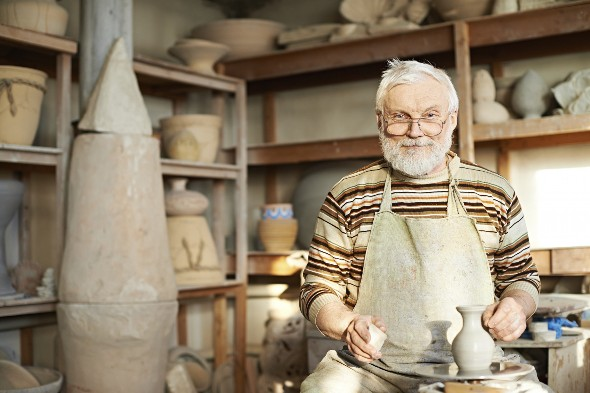 Experienced craftsman creating ceramic jug