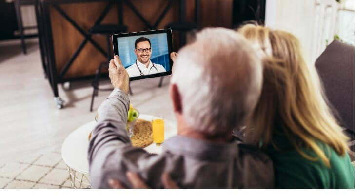Elderly couple has a video conference with their primary care physician