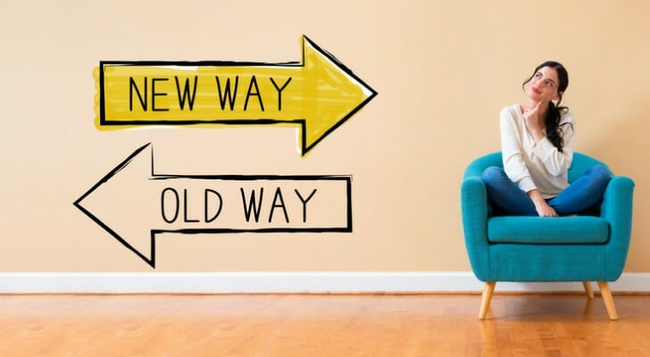 """""""New Way"""" and """"Old Way"""" signs pointed in opposite directions"""