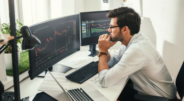 A man sits at a desk looking at two screens of financial market charts and graphs as he mulls what moves to make
