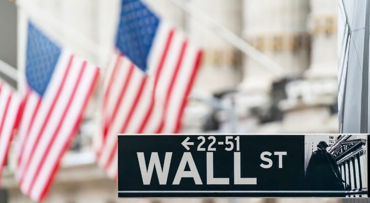 American flags with Wall Street sign in the foreground