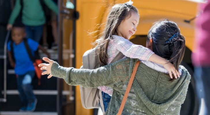 Image shows a young child wearing a light pink shirt and gray backpack hugging a guardian after school; another young child disembarks the yellow school bus in the background. SmartAsset analyzed data for 200 U.S. metro areas to find the best places to raise kids.