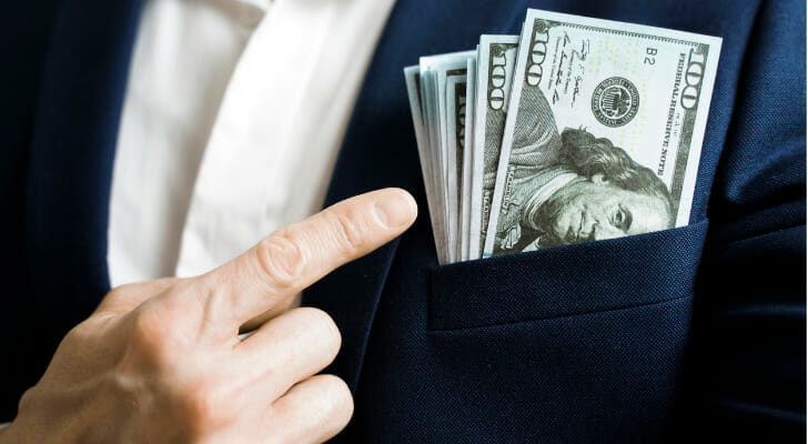 Image shows a stack of $100 bills in the front pocket of a person's blazer, with the person's finger pointing to the money. SmartAsset used IRS data to conduct the latest edition of its study on the states with the largest increases in million-dollar earners.