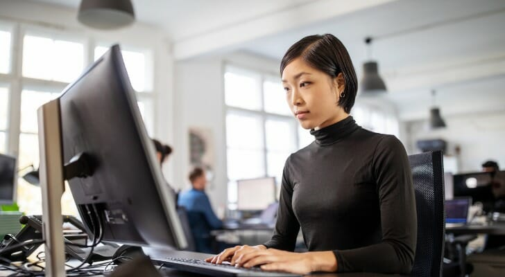 Image shows a woman tech worker at her desk working at a computer. SmartAsset analyzed various data points to conduct its latest study on the best cities for women in tech.