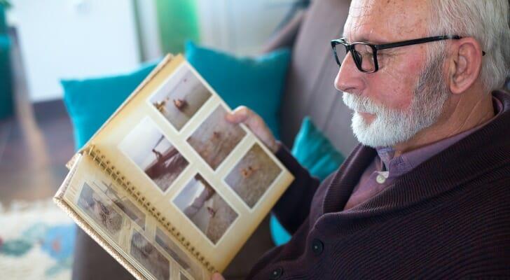 Retired man looks at family photo album