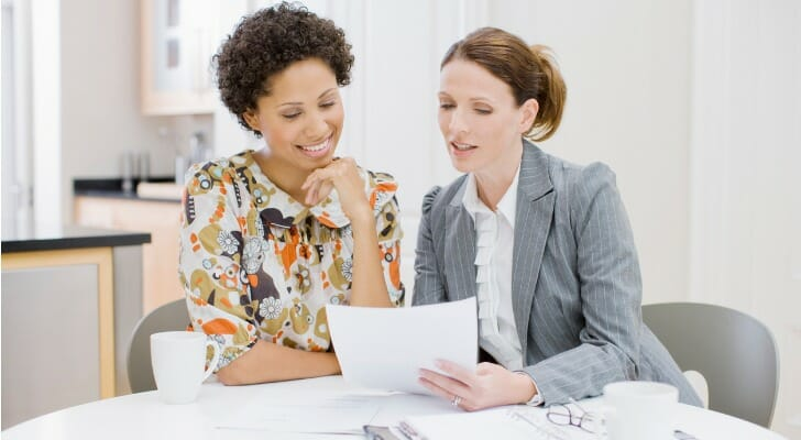Two women work on their investments