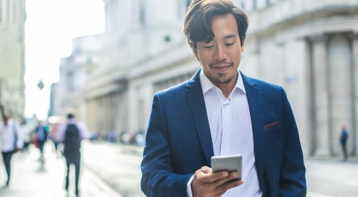 Man checks his investments on his mobile device