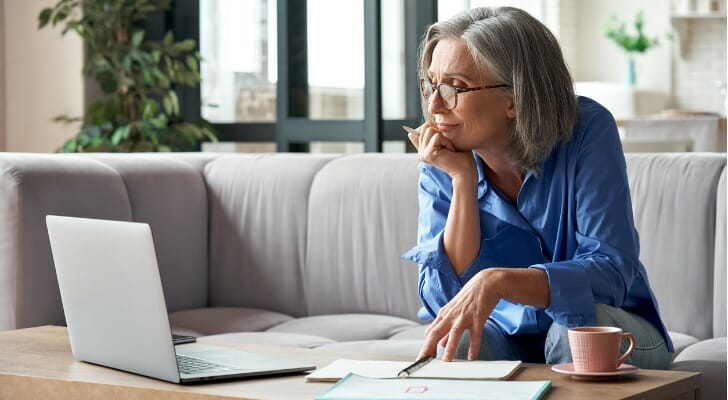 Senior woman checks her tax-deferred investment account