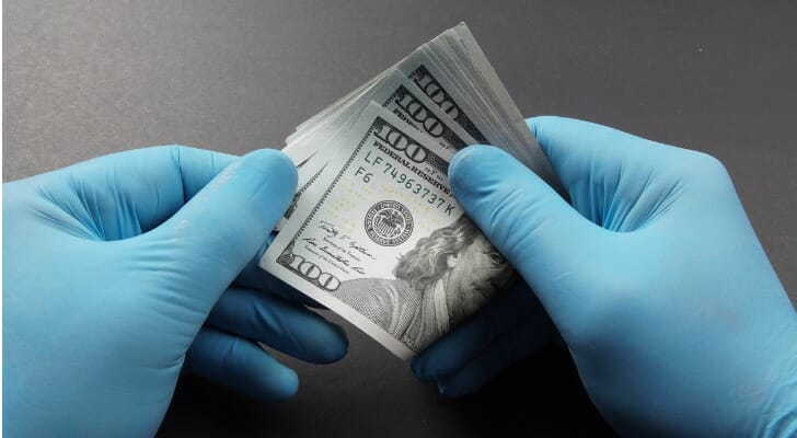 Gloved hands holding a wad of $100 bills