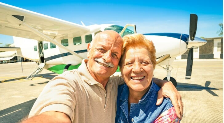 Retired couple in front of their plane