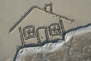 House drawn in sand, swept away by tide