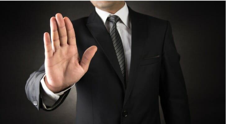 """Businessman signaling """"stop"""""""