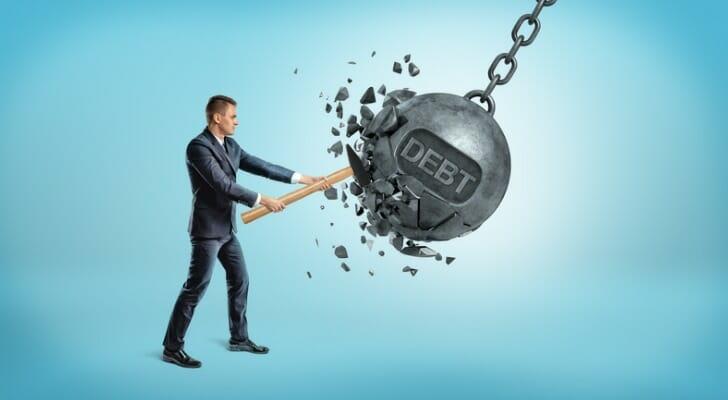 """Man smashing a """"debt ball"""""""