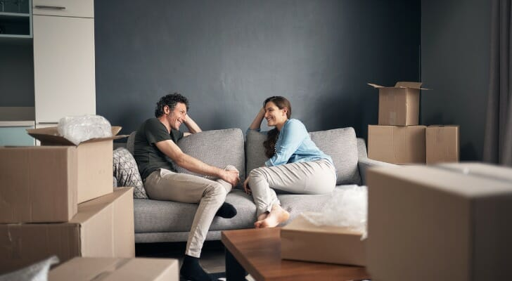 Image shows two new homeowners surrounded by unpacked boxes and sitting on a beige couch, talking happily. The couch sits on a wooden floor and against a gray wall. SmartAsset analyzed various data points in this study to find the best states for homeowners.