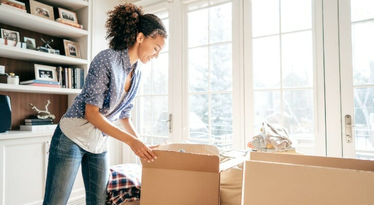 Image shows a woman unpacking moving boxes in her new home. SmartAsset analyzed CFPB data to conduct its latest study on the metro areas where women are buying the most homes.