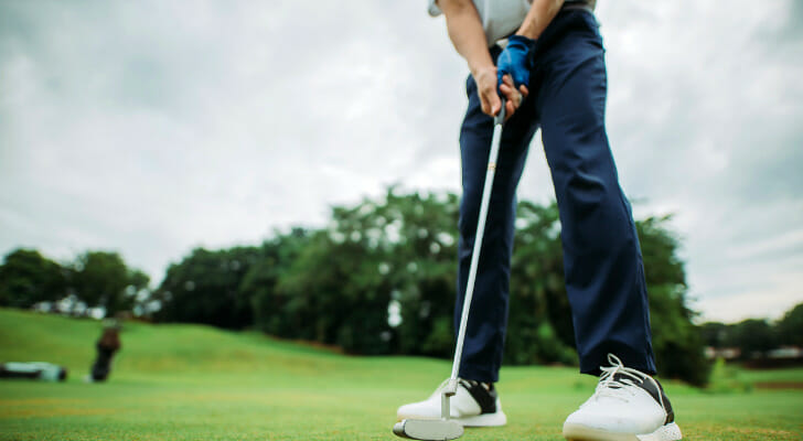 Image shows a golfer standing on a golf course, holding a club and getting ready to swing. SmartAsset analyzed various datasets to identify the best cities for golfers.