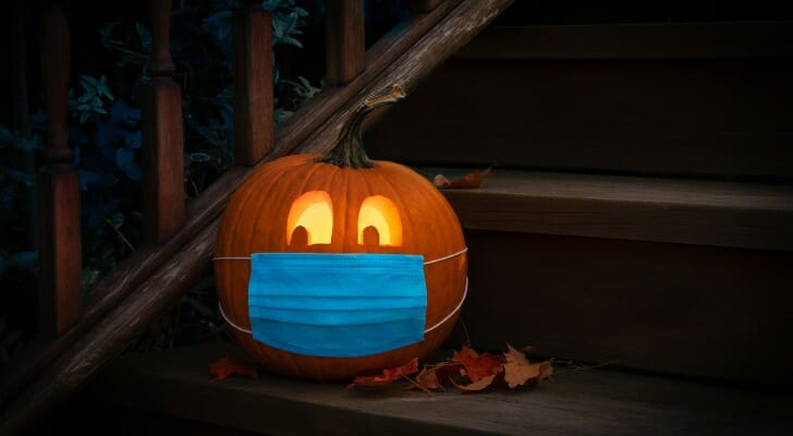 Image shows a carved and lit jack-o-lantern wearing a medical mask and sitting on some steps outside, surrounded by fallen leaves. SmartAsset analyzed various data sources (taking into account COVID-19) to find the best places to celebrate Halloween in 2020.