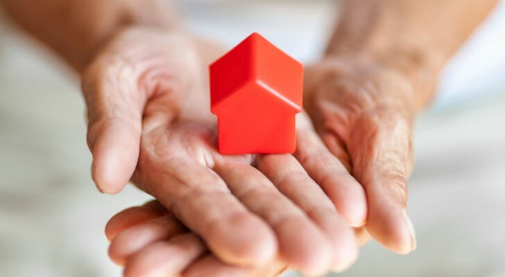 Elderly woman holds a model of a house in her hands