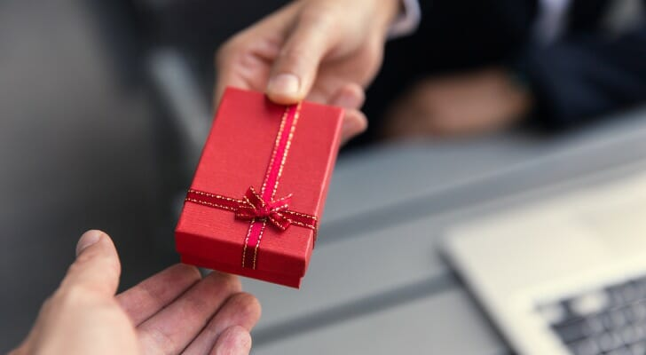 Image shows one person offering a boxed holiday gift to another person; only their hands are visible in the frame. In this study, SmartAsset took a closer look at financial advisors' plans for sending client gifts this year.