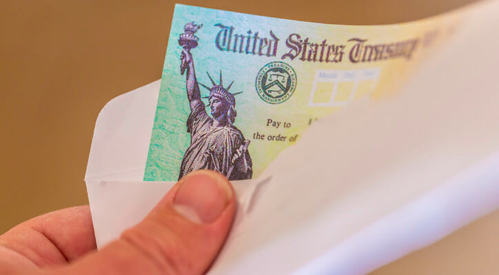 Image shows a hand holding an envelope from which a check from the U.S. Treasury is partially visible. SmartAsset analyzed Census data to conduct its latest study on the cities where retirees rely most on Social Security.