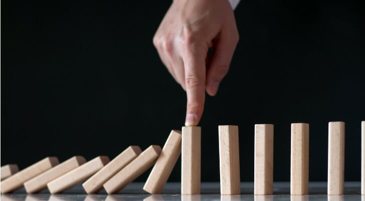 Man's hand keeps dominos from falling
