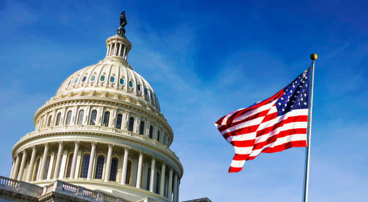Image shows the U.S. flag waving outside with the Capitol building in the background. SmartAsset analyzed various data sources to conduct its latest study on the states that are most dependent on the federal government.