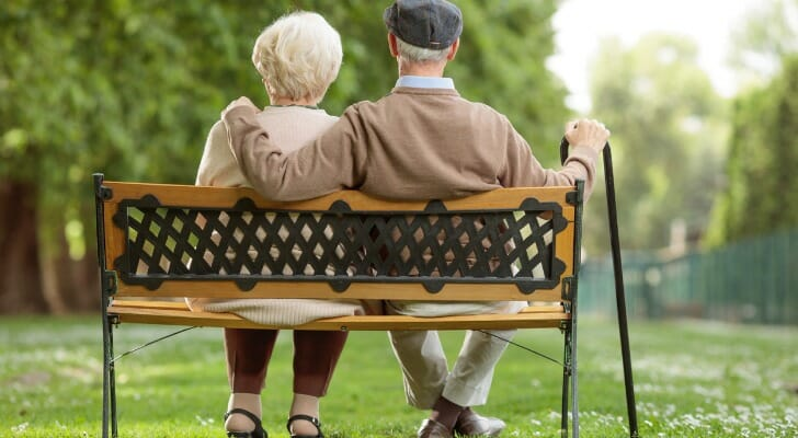 A retired couple on a park bench