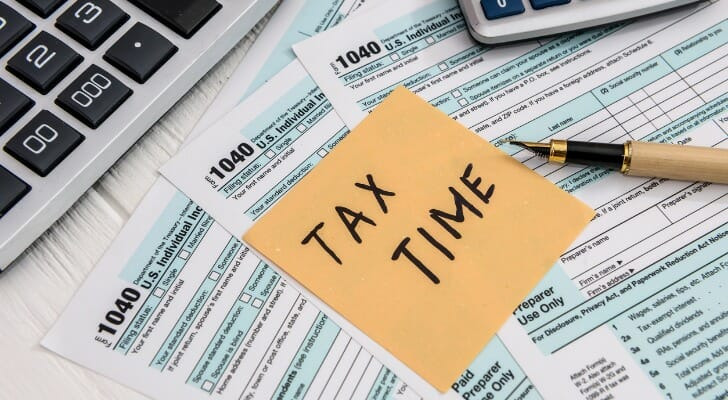 """Image shows a memo with the note """"Tax Time"""" on top of multiple copies of Form 1040, and a calculator next to it. SmartAsset analyzed IRS data to conduct its latest study on the states with the largest tax bills."""
