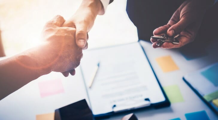 Image shows two people's hands shaking above a desk with a contract on it; one of the people is also holding a set of house keys. SmartAsset analyzed data to find the metro areas where it pays off to negotiate on home price.