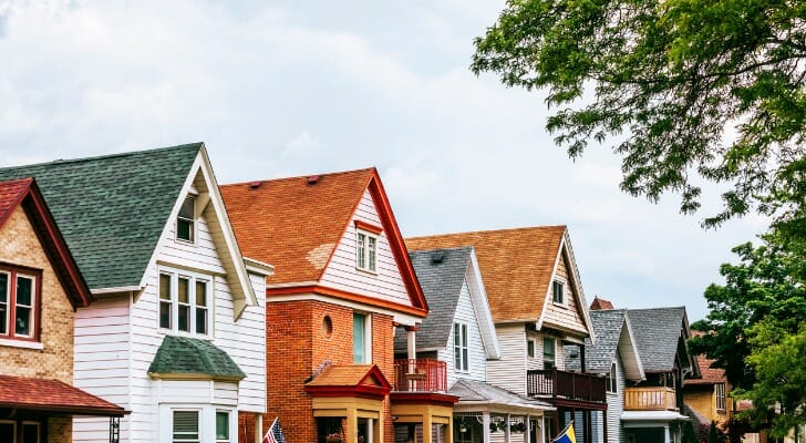 Image shows a row of eight houses on a suburban American street; only the top halves of the facades are visible and they each have a different colored pointed roof. In this study, SmartAsset analyzed various datasets to identify the best states for the middle class.