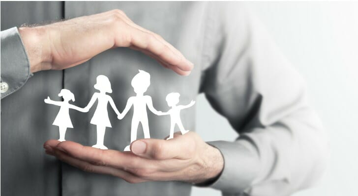 Man holding paper cutout of a family