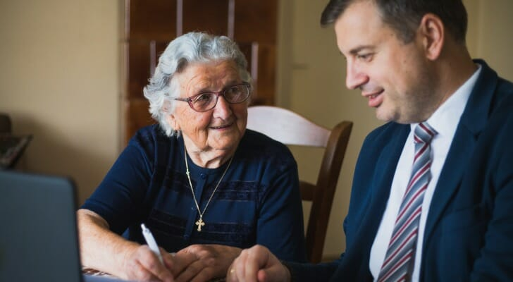 Elderly home owner signs her will in front of a lawyer